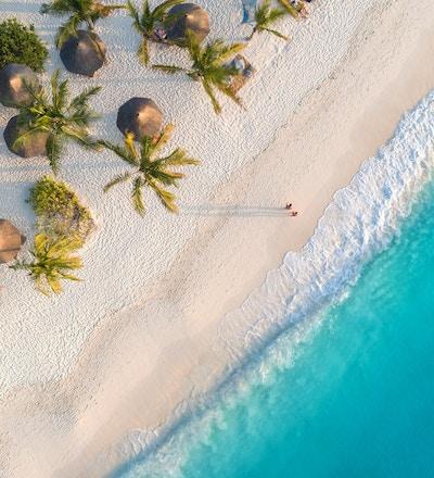 Luftfoto av parasoller, palmer på sandstranden i Indiahavet ved solnedgang. Sommerferie i Zanzibar, Afrika. Tropisk landskap med palmer, parasoller, hvit sand, blått vann, bølger. Topp utsikt