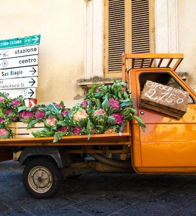 En søt oransje vintagebil som selger lilla blomkål på en gate i Sicilia, Italia. Gul vegg, skodder og veiskilt i bakgrunnen.