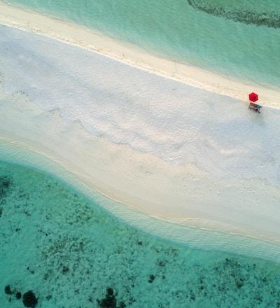 En ensom, rød paraply på den vakre stranden på en bitteliten øy i Sør Ari-atollen på Maldivene