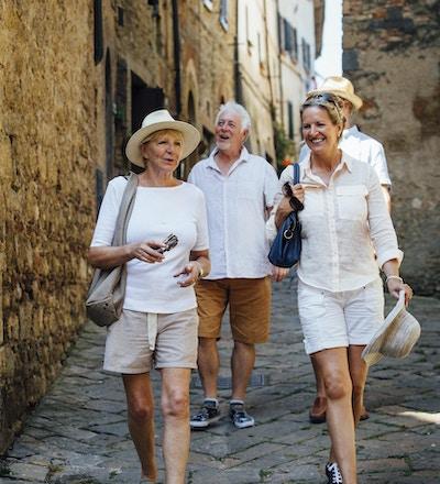 Eldre vennepar som ser seg rundt i gamlebyen i Italia. De går nedover en smal gate mens de er på ferie.