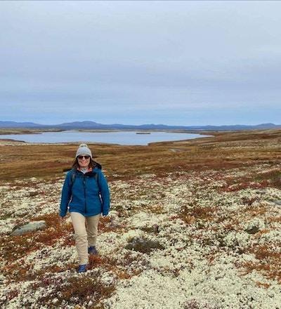 Kvinne ikledd fritidsklær og lue går ute i naturen på mose og med innsjø i bakgrunnen