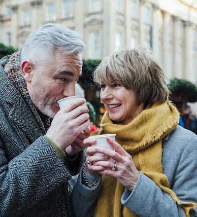 Eldre par drikker varme drikker i et julemarked i byen.