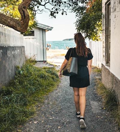 Jente med hestehale og svart kjole på vei ned i et smug mot stranden