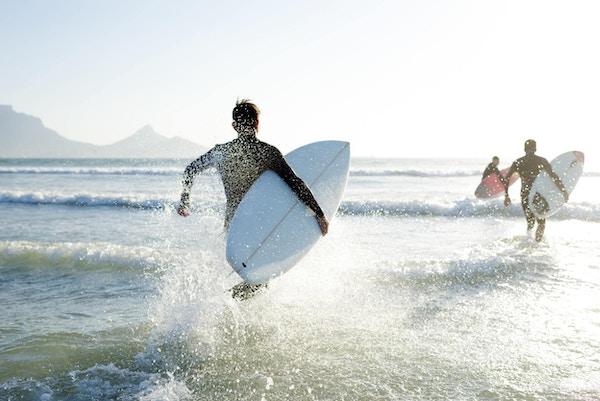 Tre tenåringsgutter som har på seg våtdraktene sine med surfebrettene, løper ut i havet på en solrik sommerdag.