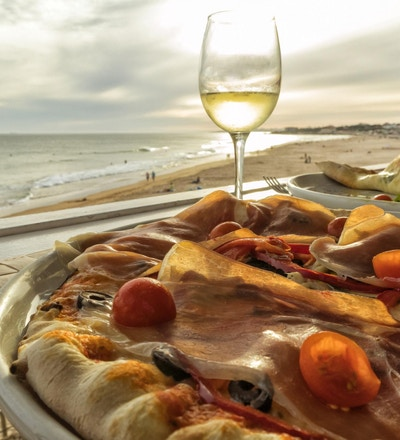 Hjemmelaget pizza med skinke, tomat, oliven og paprika med et glass hvitvin og stranden ved solnedgang i bakgrunnen