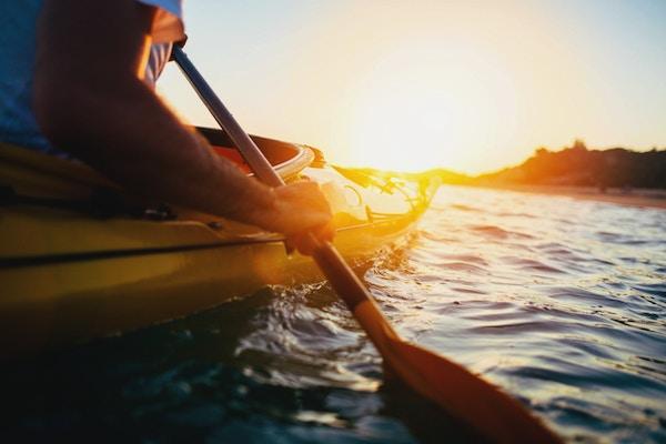Nærbilde av mannen som holder kajakkpadle ved solnedgang.