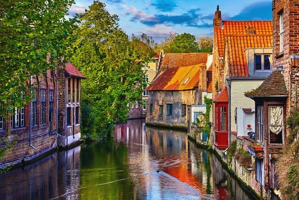 Brugge, Belgia. Middelalderske gamle hus laget av gamle murstein ved vannkanal med båter i gamlebyen. Sommersolnedgang med solskinn og grønne trær. Pittoreske landskap.
