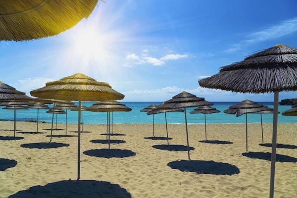 Stråparaplyer på stranden under en lys sol. Vannet i Middelhavet er turkis, krystallklart og sanden er gylden. Noen få skyer fullfører kystlandskapet.