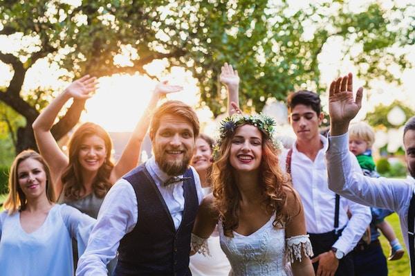Bryllupsmottakelse i hagen. Familiefeiring. Brudeparet og gjestene deres poserer ved solnedgang.