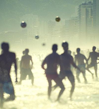 En gruppe mennesker spiller volleyball i solen på stranden