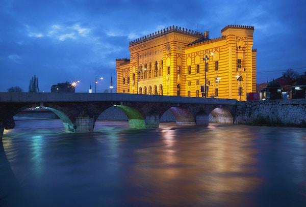 Langt eksponeringsbilde av Miljacka-elven, Seher-Cehaja-broen (bygget i 1586) og rådhuset eller nasjonalbiblioteket (bygget i 1896) i Sarajevo, Bosnia.