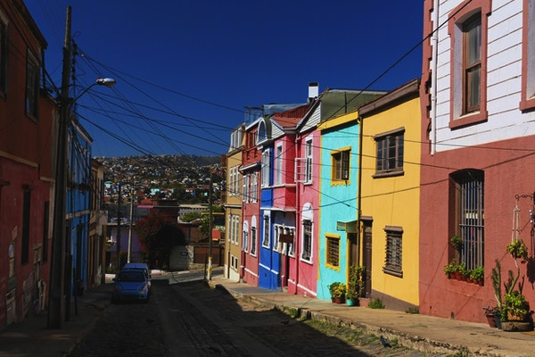 En smal bakgate med fargerike hus og utsikt mot byen