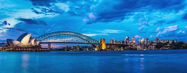 Solnedgang i Sydney med Harbour Bridge og operahuset i Sydney i bakgrunnen.