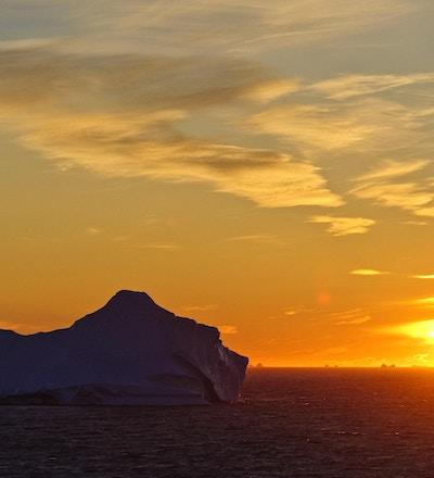 Et isfjell som driver i havet i solnedgangen