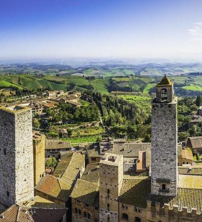Panoramautsikt over hustakene og de ikoniske steintårnene i San Gimignano, den middelalderske bakketoppsbyen som ligger blant grønne vingårder i hjertet av Toscana, Italia.