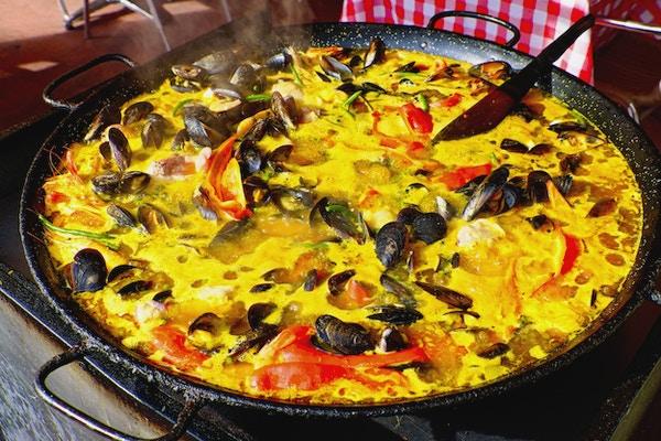 Tradisjonell spansk gatemat i Camargue, Frankrike: paella til sjømat i dampende panne med blåskjell, reker, krabbeklør, paprika (rød pepper), safran, ris og grønne bønner. Tre øse (spatel) synlig. Horisontalt, ingen mennesker, utendørs.