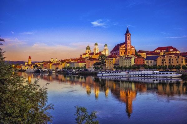 Strandpromenaden og sightseeingbåter i Passau ved solnedgang.