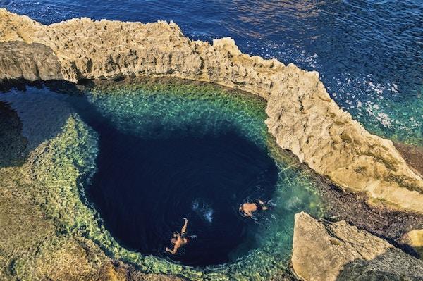 Dypblått hull ved det verdensberømte Azure Window på Gozo-øya - middelhavsunderrund på det vakre Malta - Ukjennelige turistdykkeere som svømmer til vannvannhule