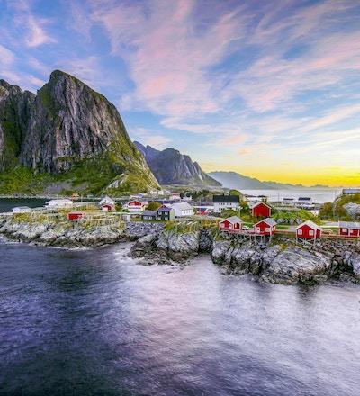 Populær utsikt over fiskehytter (rorbuer) i Hamnøy, Norge med Lilandstinden fjelltopp som bakgrunn under soloppgang