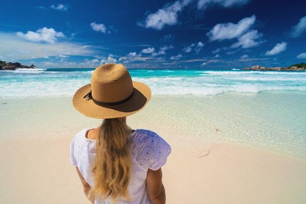 Kvinne på sandstrand på Seychellene, Afrika.