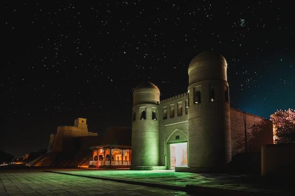 Den vestre porten (Ata Darvoza) til den gamle byen Itchan Kala om natten med stjerner. Khiva, Usbekistan