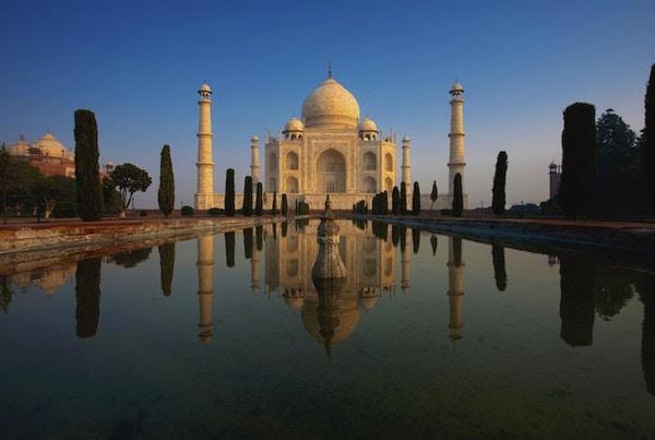 Taj Mahal lyser vakkert ved soloppgang, da den gjenspeiles i en rolig vannfontene.
