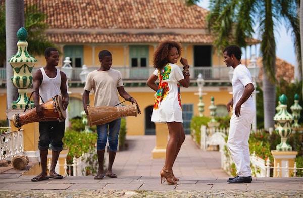 Ungt svart par danser salsa på gatene i Trinidad, Cuba mens trommeslagerne ser på dem.