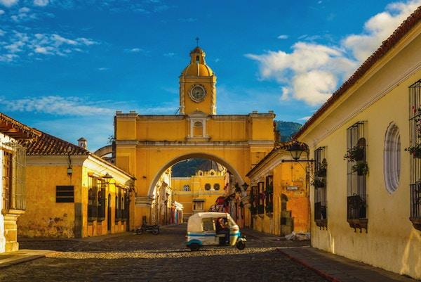 en tuk-tuk-taxi passerer inn fra Santa Archina-buen i Antigua, Guatemala.