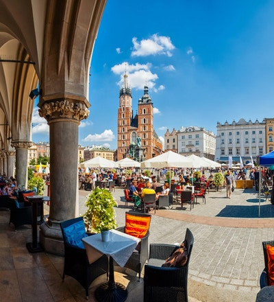 Krakow full av turister som har en kaffepause under buene i Cloth Hall