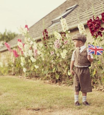 En ung britisk gutt i vintageklær feirer sin engelske arv ved å vifte med Storbritannias nasjonale flagg. Han står foran hulstokker. Vintage tonet.