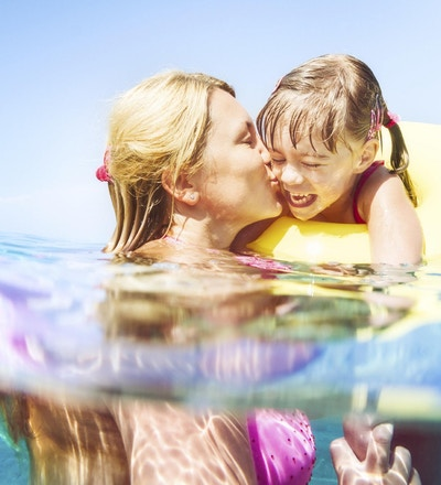 En ung jente og hennes mor svømmer i lyseblått vann på badeferie