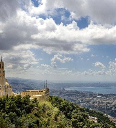 Bildet som er tatt på en delvis skyet og stormfull dag konsentrerer seg i forgrunnen på Harissa-klosteret og viser i bakgrunnen kystlinjen i byen Beirut.