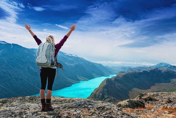 Ung turistkvinne som føler seg fri og står med hendene i været på toppen av fjellstien mens hun ser på et vakkert landskap