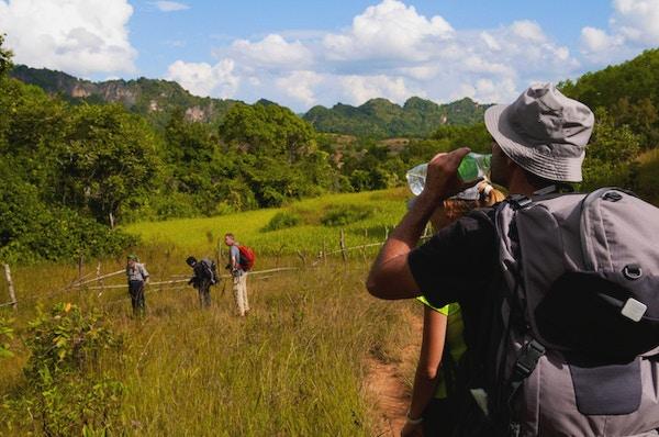 """""""En mann drikker fra en flaske vann under en tre-dagers fottur i landlige Myanmar, fra Kalaw til Inle Lake. Fire turgåere og deres guide er på bildet:"""""""
