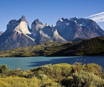 Stupbratte fjell under skyfri himmel med en innsjø i forgrunnen