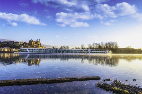 Elvecruiseskip på elv mot slott i morgenstemning