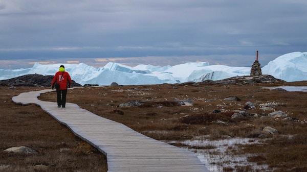 En rødkledd turist som vandrer på en sti, med store isfjell og grå himmel i bakgrunnen