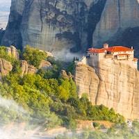 En bygning ruver over landskapet fra en øde klippe. Foto