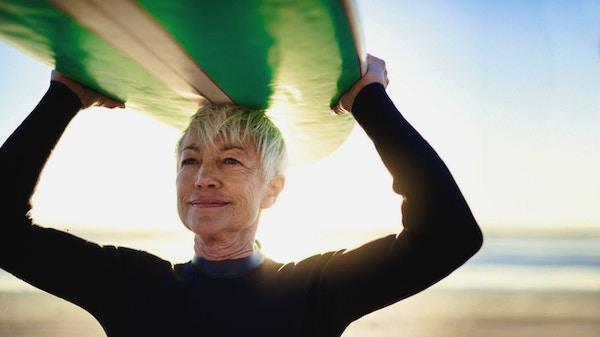 Beskjæret skudd av en eldre kvinne som holder et surfebrett på toppen av hodet på vei til å surfe