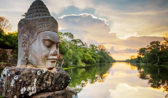 Steinansiktet Asura på hovedveien nær South Gate of Angkor Thom i Siem Reap, Kambodsja. Vakker solnedgang over en eldgammel vollgrav i bakgrunn. Den mystiske Angkor Thom er en populær turistattraksjon.