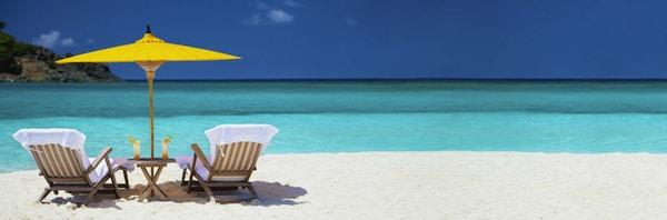 Panoramabilde av teakstoler under en gul kinesisk paraply på en tropisk strand i Karibien