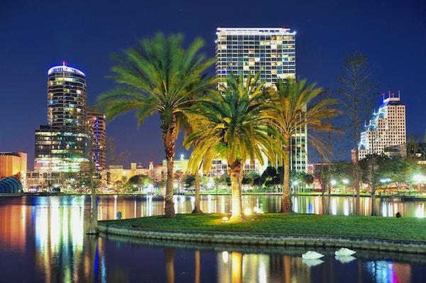 Orlando skyline panorama over Eola-sjøen om natten med urbane skyskrapere, tropiske palmer og klar himmel.