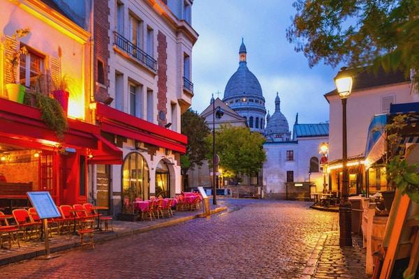Gate med uterestauranter og Sacre Coeur i kveldsstemning