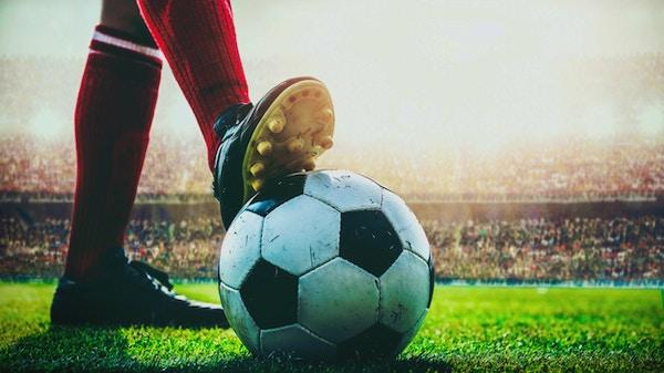 føtter av fotballspiller tråkker på fotball for avspark på stadion