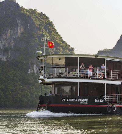 Elvecruiseskip på elven med mennesker på dekk og grønne åser i bakgrunnen. Foto.