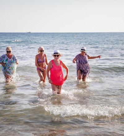 Liten gruppe eldre kvinner som morer seg i havet. Sommerdag på Kypros.