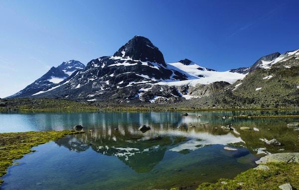 Liten innsjø i Jotunheimen nasjonalpark i Norge. Fjellet gjenspeiles i vannet. Fotomerge på fire skudd.