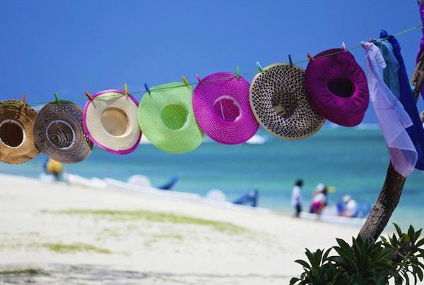 Detaljhandel på stranden, mauritansk stil. Halmhatter og strandomslag for salg på en tropisk strand på en varm, solrik dag i paradis, også kalt Mauritius. Turister i bakgrunnen som leier en pedalbåt for å padle i det turkise vannet i den naturlige lagunen.