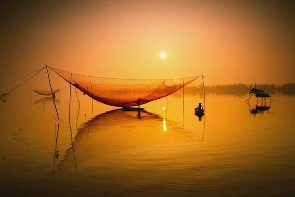 Uidentifisert fisker sjekker garnene sine tidlig om morgenen på elven i Hoian, Vietnam