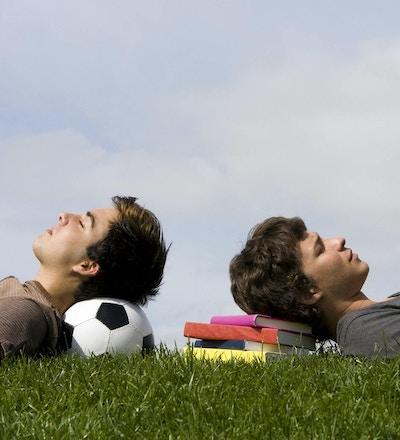 Gutter ligger med hodet på bøker og en ball